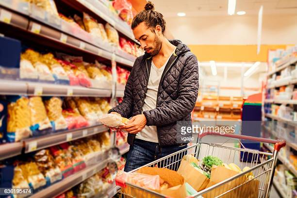 young bearded man in a supermarket. - ingredient stock pictures, royalty-free photos & images