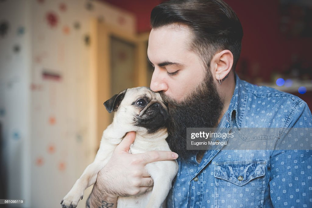 Young bearded man kissing dog in arms : Stock Photo