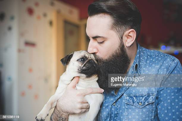young bearded man kissing dog in arms - homme soumis photos et images de collection