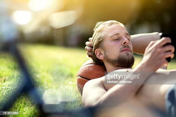 Young bearded man lying in grass using phoneu