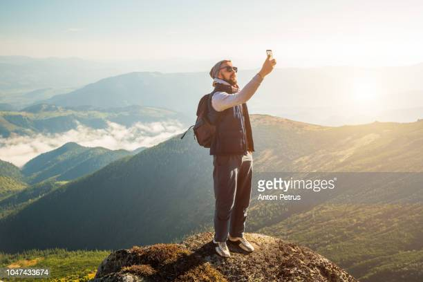young bearded man makeing selfie in the mountains at dawn - ukraine landscape stock pictures, royalty-free photos & images