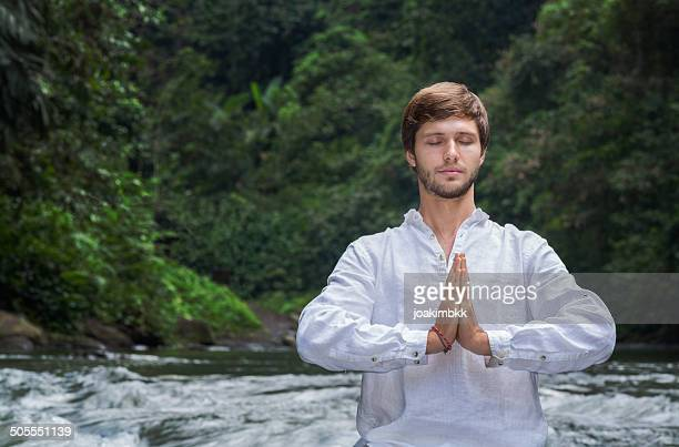 Young bearded man meditating by the river