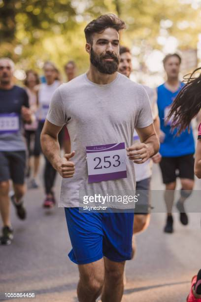 young bearded man running a marathon race in nature. - half_marathon stock pictures, royalty-free photos & images