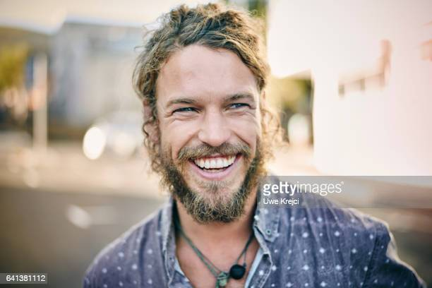 young bearded man smiling - lachen stock-fotos und bilder