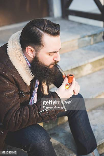 Young bearded man smoking pipe on steps