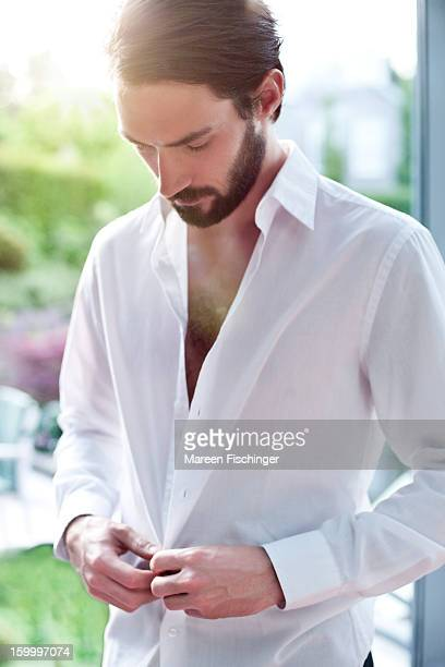 A young bearded man unbuttoning his shirt