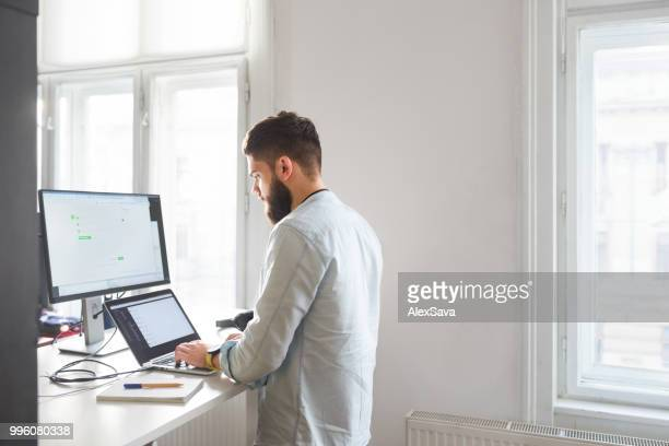young bearded man working at his office - stare in piedi foto e immagini stock