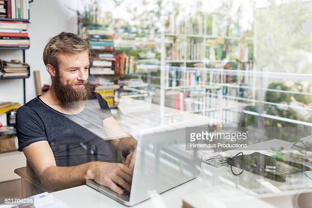 young bearded man working at home office - laptop stock-fotos und bilder