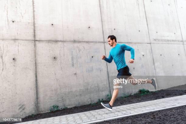 junge bärtige sportler läuft treppen im freien - rennen sport stock-fotos und bilder