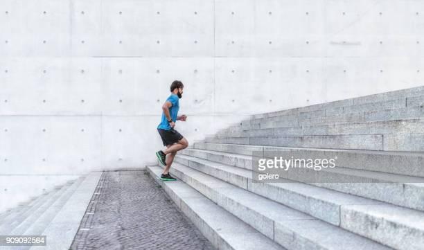 junge bärtige sportler läuft treppen im freien - stufen stock-fotos und bilder