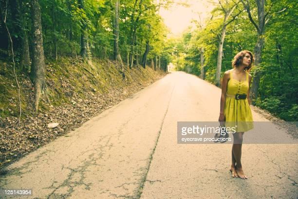junge schöne erwachsene frau auf die rural road ab - gelbes kleid stock-fotos und bilder
