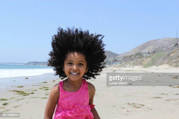 Young, beautiful African American girl with black curly hair enjoys a day at the beach in California  wearing a bright pink dress