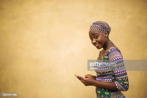 enviar mensajes de texto áfrica hermosa niña en su teléfono móvil en espacio de copia de cámara - áfrica del oeste fotografías e imágenes de stock