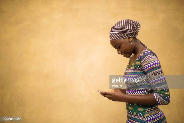 enviar mensajes de texto áfrica hermosa niña en su teléfono móvil sonriendo contra un espacio de la copia de fondo tradicional marrón cálido - áfrica del oeste fotografías e imágenes de stock