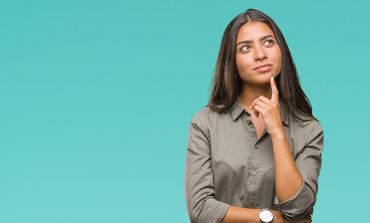Young beautiful arab woman over isolated background with hand on chin thinking about question, pensive expression. Smiling with thoughtful face. Doubt concept. 1046571034