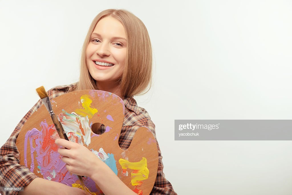 Young beautiful artist posing with a palette : Stock Photo