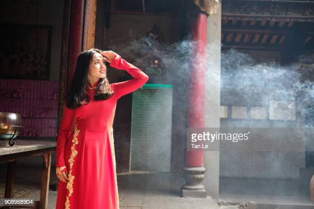 young beautiful asian girl is wearing the red ao dai in a pagoda. - thien hau pagoda stock pictures, royalty-free photos & images