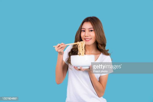 young beautiful asian woman eating yummy hot and spicy instant noodle using chopsticks isolated on cyan background. asian girl open of the month with cheap food. - タイ人 ストックフォトと画像