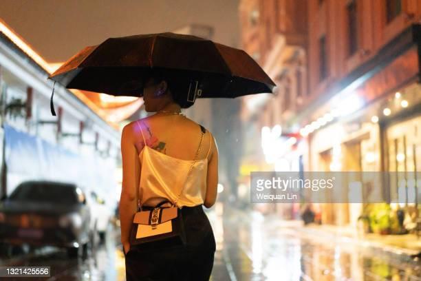 a young beautiful asian woman holding an umbrella walking on a city street - solo adulti foto e immagini stock