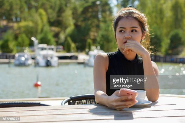 Young beautiful Asian woman relaxing against view of the pier