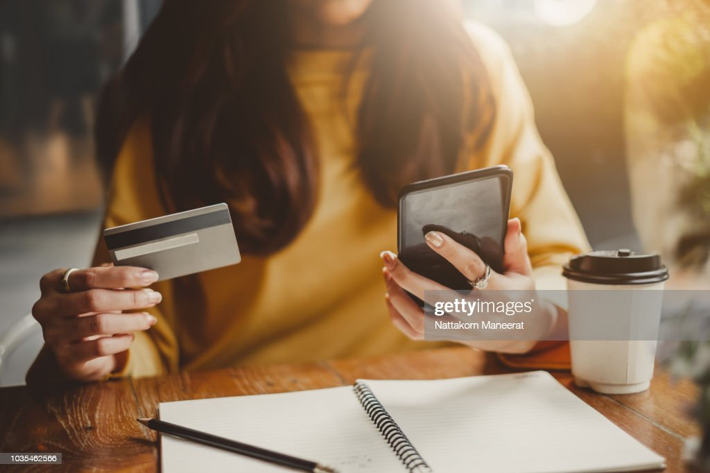 Young beautiful asian woman using smart phone and credit card for shopping online in coffee shop cafe, vintage tone color : Stock Photo