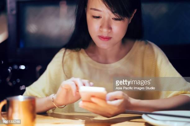 Belle jeune femme asiatique à l'aide de téléphone intelligent dans la nuit