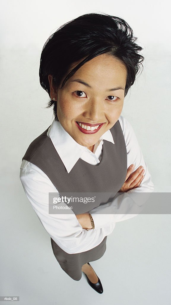 young beautiful asian woman with short dark hair in a white blouse and grey vest stands looking up at the camera with her arms crossed : Foto de stock