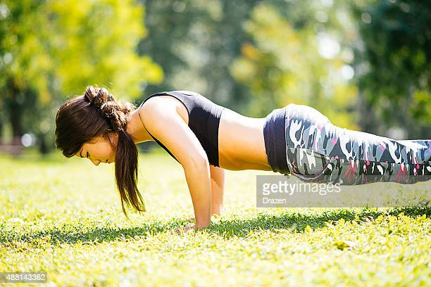 young beautiful athlete woman doing push ups in outdoor training - beautiful bums stock photos and pictures