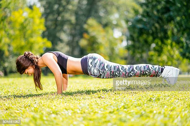 young beautiful athlete woman doing push ups in outdoor training - beautiful female bottoms stock photos and pictures