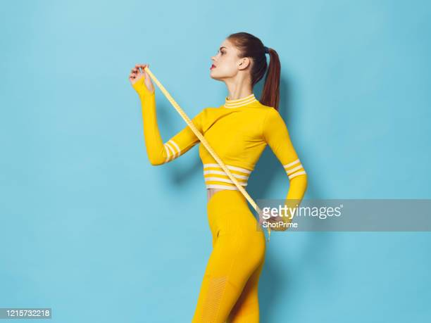 young beautiful athletic woman measure her figure with a measuring tape - championships stock pictures, royalty-free photos & images