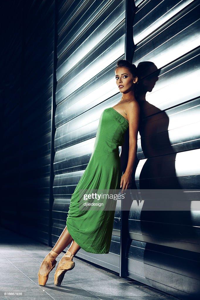 Young beautiful ballerina posing at night next to the futuristic : Stock Photo