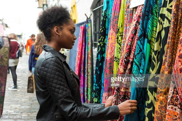 junge schöne schwarze frauen einkaufen auf dem wochenmarkt tuch - erschwinglich stock-fotos und bilder
