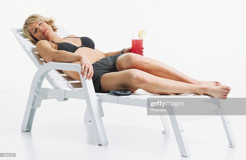 young beautiful blonde caucasian adult female wearing a dark bikini top and matching shorts lies relaxing on a patio lounge chair with her eyes closed as she holds a glass of pink lemonade and listens to a portable cd player : Foto de stock