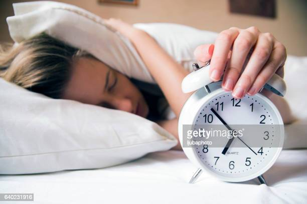 young beautiful blonde woman lying in bed suffering from alarm - alarm stock photos and pictures