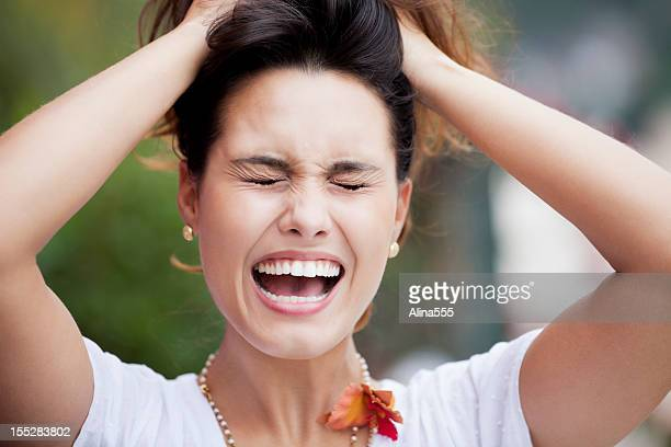 young beautiful brazilian woman screaming and pulling her hair - pulling hair stock photos and pictures