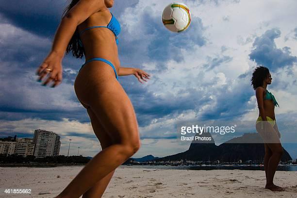 Young beautiful Brazilian women play soccer at Botafogo beach Sugar Loaf mountain in background