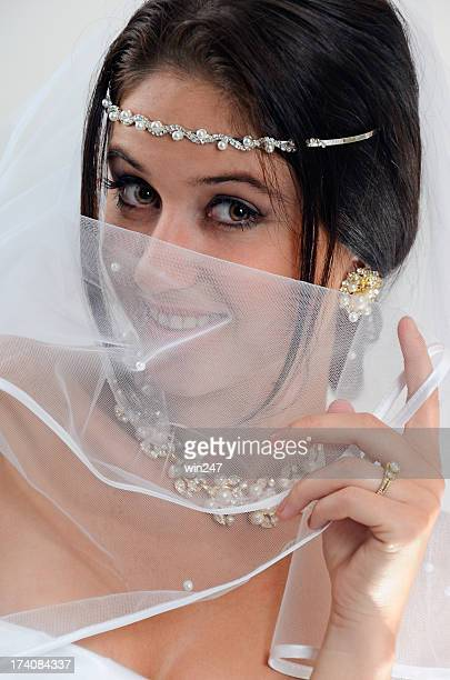 Young Beautiful Bride Smiling Behind White Veil