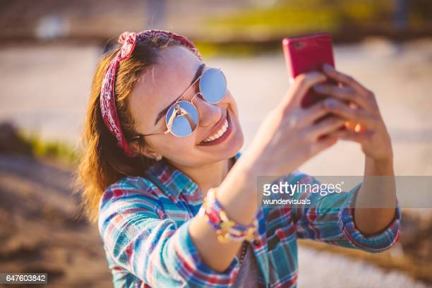 Young beautiful brunette taking a selfie at the beach