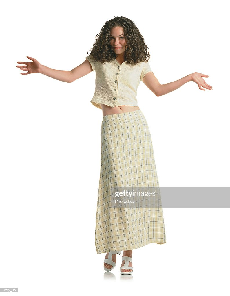 young beautiful brunette teenage girl with curly hair wearing a cream plaid skirt and cream short shirt steps toward the camera and gives a slight smile as she holds her hands and arms out to the side : Foto de stock