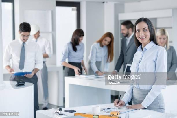 Jonge mooie zakenvrouw permanent door Bureau op kantoor