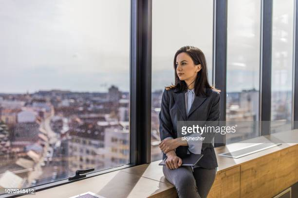 Día joven empresaria hermosa soñando por la ventana.