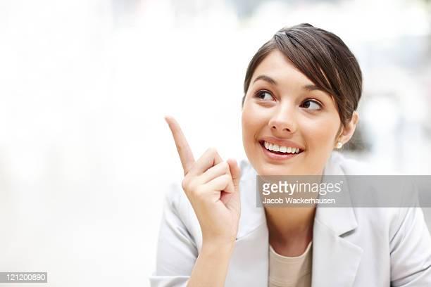 Junge schöne Geschäftsfrau zeigt mit copyspace