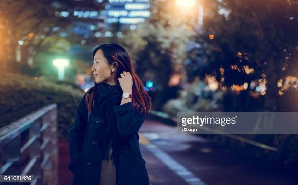 Young beautiful businesswoman walking in the city at night.