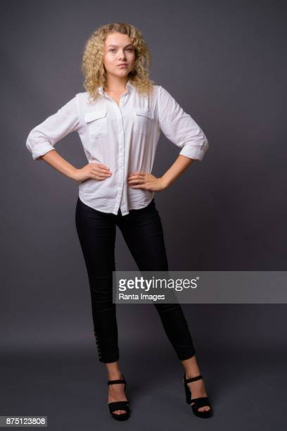 Young beautiful businesswoman with blond curly hair against gray background