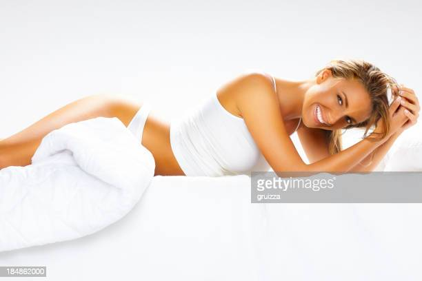 Young, beautiful, cheerful blonde woman relaxing on bed