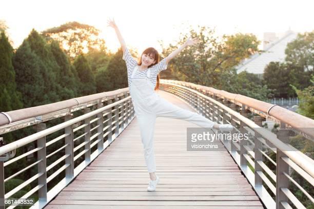 jeune belle fille chinoise posant à la passerelle dans le parc
