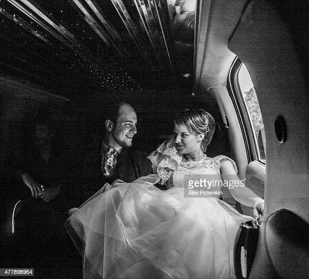 Young beautiful couple, bride and groom, in the limousine. Wedding.