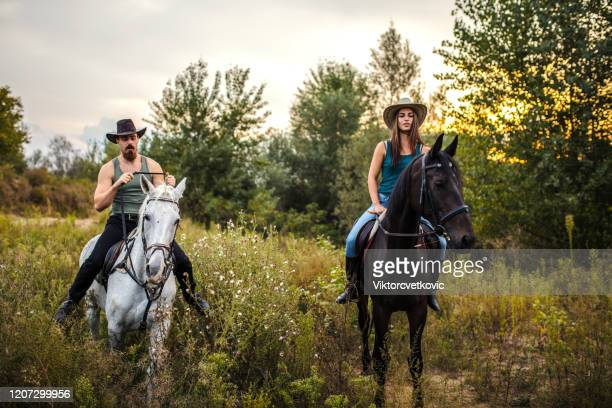 young beautiful couple enjoys riding horses in nature - equestrian eventing stock pictures, royalty-free photos & images