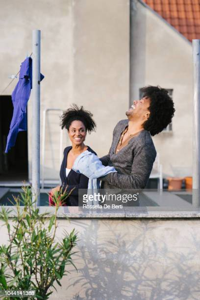 Young beautiful couple hanging up laundry on rooftop terrace