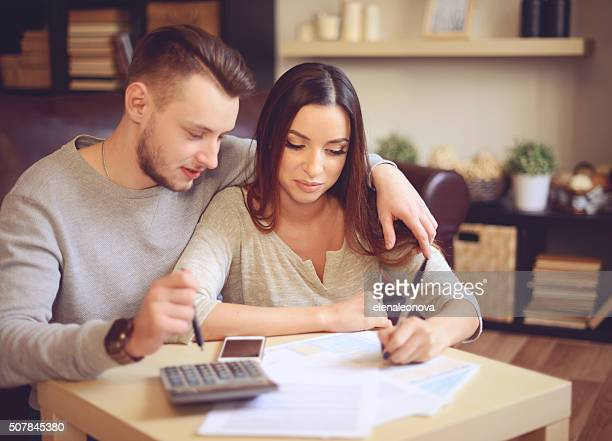 young beautiful couple in home interior - 1040 tax form stock photos and pictures